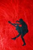 Siluetta di una donna con una chitarra su un lerciume, fondo rosso Fotografia Stock