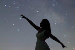 Siluetta di una donna di dancing che indica in cielo notturno Siluetta nell'ambito della notte stellata, galassia Defocused della immagine stock