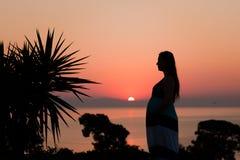 Siluetta di una donna incinta sulla spiaggia al tramonto Fotografia Stock Libera da Diritti