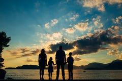 Siluetta di una famiglia con i bambini contro il contesto del tramonto e del mare Fotografia Stock Libera da Diritti