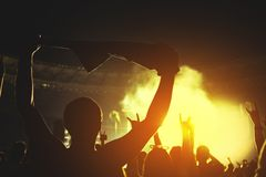 Siluetta di una folla di concerto Il pubblico applaude i musicisti in scena Il riflettore luminoso e la gente ballante fotografie stock libere da diritti