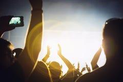 Siluetta di una folla di concerto Il pubblico applaude i musicisti in scena Il riflettore luminoso e la gente ballante fotografia stock libera da diritti