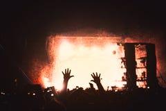 Siluetta di una folla di concerto Il pubblico applaude i musicisti in scena Il riflettore luminoso e la gente ballante fotografia stock