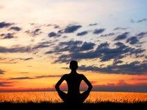 Siluetta di una giovane donna che medita su tramonto Fotografia Stock