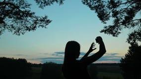 Siluetta di una giovane donna che prende selfie con il suo telefono dopo il tramonto video d archivio