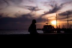 Siluetta di una giovane donna contro bello colore porpora del cielo di sera Fotografia Stock Libera da Diritti