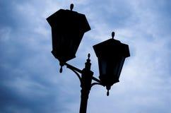Siluetta di una lampada di via nei precedenti di un cielo tempestoso Immagine Stock