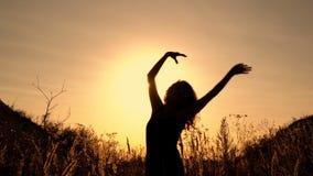Siluetta di una ragazza che balla ed ondeggia le sue mani al tramonto all'aperto Fine in su 4K archivi video