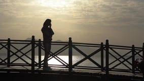 Siluetta di una ragazza che rivolge allo smartphone vicino al mare al rallentatore archivi video