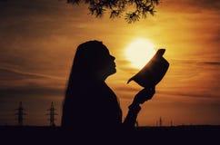 Siluetta di una ragazza con un cappello sui precedenti del tramonto fotografia stock libera da diritti