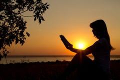 Siluetta di una ragazza con un libro in mani al tramonto Fotografia Stock