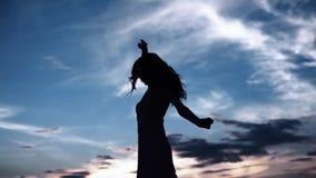 Siluetta di una ragazza di dancing su un tramonto del fondo bella ragazza che balla e che si diverte all'aperto stock footage