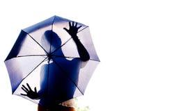 Siluetta di una ragazza dietro un ombrello fotografia stock