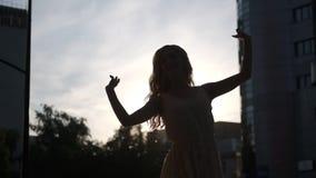 Siluetta di una ragazza esile che balla all'aperto nella città video d archivio