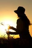 Siluetta di una ragazza nel campo con le orecchie fotografie stock libere da diritti