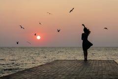 Siluetta di una ragazza su un'alba del fondo di tramonto sul mare fotografia stock