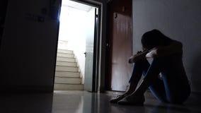 Siluetta di una ragazza triste che si siede nello scuro che pende contro la parete in vecchio condominio, violenza domestica, pro video d archivio
