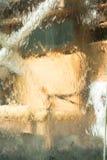 Siluetta di una sedia marrone attraverso un vetro bagnato Fotografia Stock