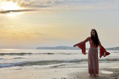 Siluetta di una signora alla moda che posa ad una spiaggia inglese al tramonto fotografia stock