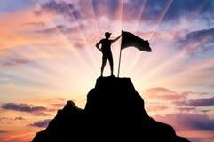 Siluetta di uno scalatore con una bandiera sulla cima della montagna che ha sottomesso fotografie stock
