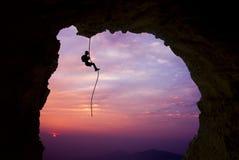 Siluetta di uno scalatore sopra il bello tramonto Immagini Stock Libere da Diritti