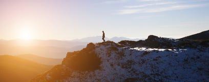 Siluetta di uno scalatore su una cresta della montagna Immagine Stock