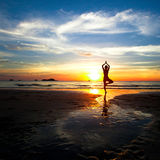 Siluetta di yoga di pratica della donna sulla spiaggia Fotografie Stock