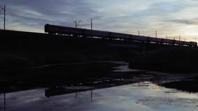 Siluetta e riflessione del ponte di incrocio del treno sul tramonto stock footage