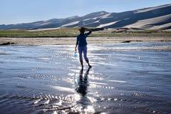 Siluetta e riflessione della donna in acqua luccicante Fotografia Stock Libera da Diritti