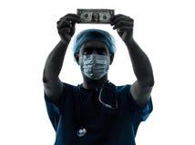 Siluetta examing della banconota in dollari dell'uomo del chirurgo di medico Fotografia Stock
