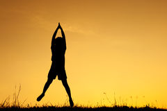 Siluetta felice di salto e di tramonto della donna Fotografia Stock Libera da Diritti