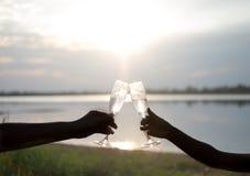 Siluetta Gli amanti passano con i vetri di champagne contro i precedenti del cielo e del tramonto immagini stock libere da diritti