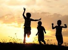 Siluetta, gruppo di bambini felici Immagini Stock