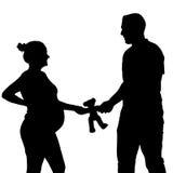 Siluetta incinta con l'orsacchiotto Fotografia Stock