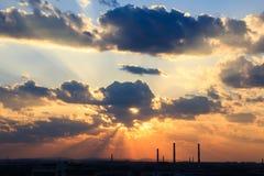 Siluetta industriale della città contro il cielo su un tramonto Fotografia Stock