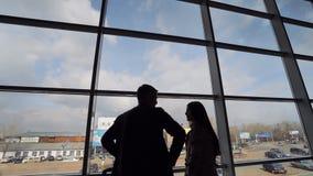 Siluetta maschio e femminile dentro la costruzione dell'aeroporto nel fondo della città video d archivio