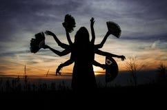 siluetta Multi-armata con i fan sul fondo di tramonto fotografia stock
