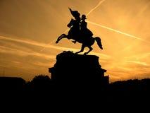 Siluetta nera del monumento del cavaliere del cavallo su fondo del tramonto giallo Immagini Stock