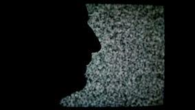 Siluetta non rasata di profilo dell'uomo davanti al fondo statico di rumore della TV video d archivio