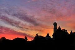 Siluetta rossa ed arancio del villaggio di tramonto, paesaggio dell'ombra con la chiesa fotografia stock libera da diritti