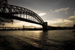 Siluetta scura del ponte del ponte e di Triborough del portone dell'inferno sopra il fiume nello stile d'annata immagine stock