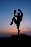 Siluetta scura di un pugile maschio muscolare all'aperto sul tramonto Fotografie Stock Libere da Diritti