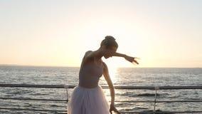 Siluetta splendida del ballerino di balletto che pratica all'aperto La ragazza in tutu bianco che sta in sole rays seaside archivi video