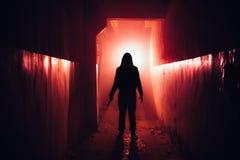 Siluetta terrificante con il coltello nella costruzione abbandonata illuminata rosso scuro Orrore circa il concetto del maniaco fotografia stock