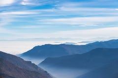 Siluetta tonificata blu della montagna e valli nebbiose nell'inverno Fotografia Stock Libera da Diritti