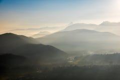 Siluetta tonificata blu della montagna e valli nebbiose nell'inverno Fotografie Stock