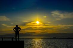 Siluetta, uomo solo che guarda il mare al tramonto Immagini Stock