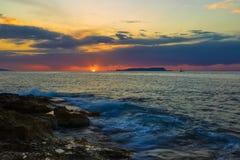 Siluetta variopinta della montagna e nave antica contro il sole arancio luminoso, nascosto dietro le nuvole blu, mare in priorità fotografia stock libera da diritti