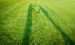 Siluette che formano un cuore sopra erba Immagine Stock