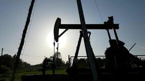Siluette de la estación de bomba de aceite en puesta del sol Tansport y distribución del aceite Tecnología del sistema de transpo almacen de video